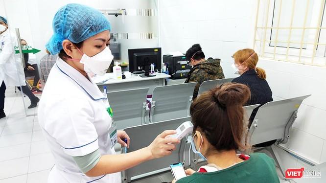 Bác sĩ kiểm tra thân nhiệt cho bệnh nhân. Ảnh: Minh Thúy