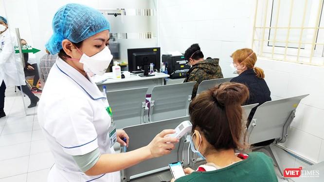 Bác sĩ đo nhiệt độ cho bệnh nhân. Ảnh: Minh Thúy