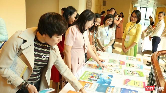 Giáo viên và phụ huynh học sinh xem bản mẫu sách giáo khoa. Ảnh: Minh Thúy