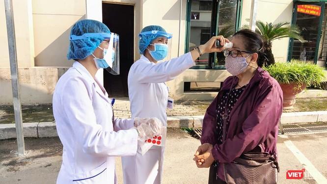 Nhân viên y tế kiểm tra nhiệt độ của người dân (Ảnh - Minh Thuý)