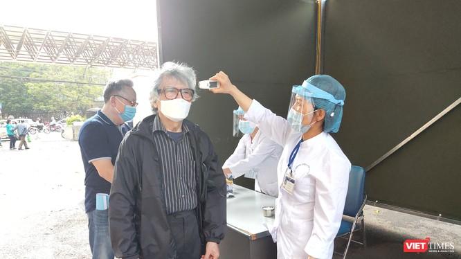 Nhân viên y tế kiểm tra thân nhiệt cho người dân (Ảnh: Minh Thuý)
