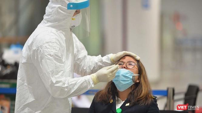 Nhân viên y tế lấy dịch mũi xét nghiệm COVID-19 cho cán bộ làm việc tại sân bay Nội Bài. Ảnh: Hoàng Anh
