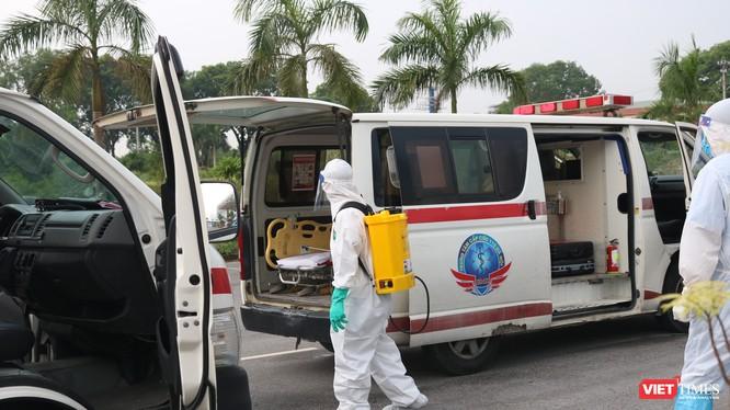 Nhân viên y tế phun khử khuẩn xe cấp cứu (Ảnh: Minh Thúy)