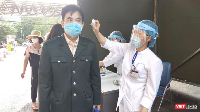 Nhân viên y tế đo nhiệt độ cho người dân trước khi vào bệnh viện (Ảnh - Minh Thuý)