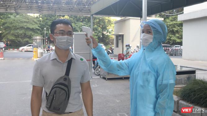 Nhân viên y tế kiểm tra nhiệt độ của người dân trước khi vào bệnh viện (Ảnh - Minh Thuý)