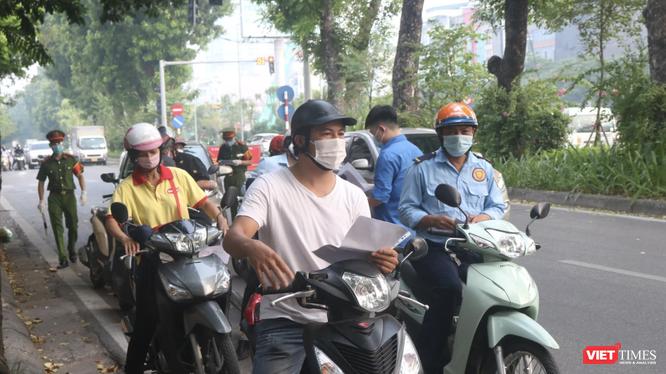 Người dân xếp hàng chờ kiểm tra giấy đi đường (Ảnh - Minh Thuý)