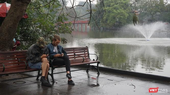 Khách du lịch tận hưởng khoảng lặng hiếm hoi trên đường phố Hà Nội.