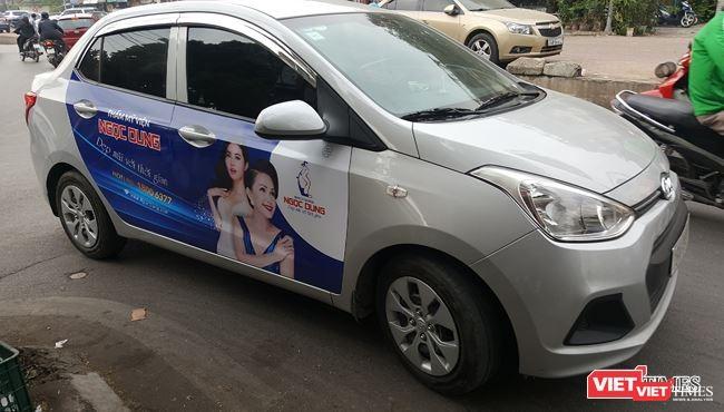 Các taxi công nghệ đều không niêm yết số điện thoại của đơn vị kinh doanh ở hai bên thân xe hoặc hai bên cánh cửa xe. Ảnh: Một xe tuân thủ việc dán logo Grab tại phía trên, bên trái của kính chắn gió nhưng không niêm yết thông tin hãng.