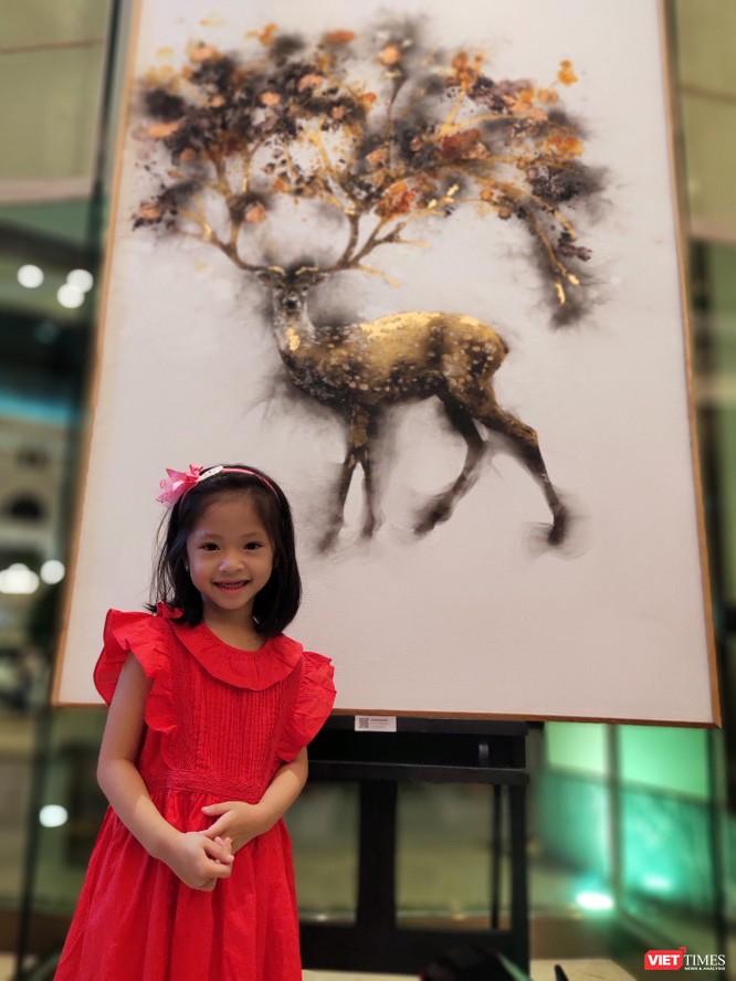 Em bé say sưa chiêm ngưỡng các tác phẩm với chủ đề thiên nhiên của họa sĩ Trung Nghĩa