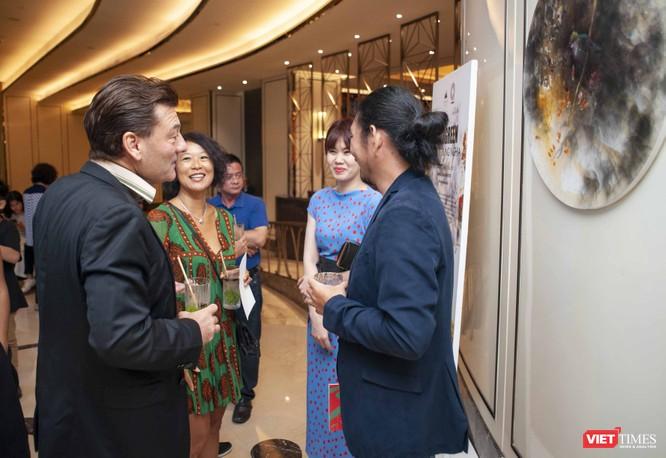 Họa sĩ Trung Nghĩa (bên phải ảnh) đang trao đổi với các khách thưởng lãm nghệ thuật