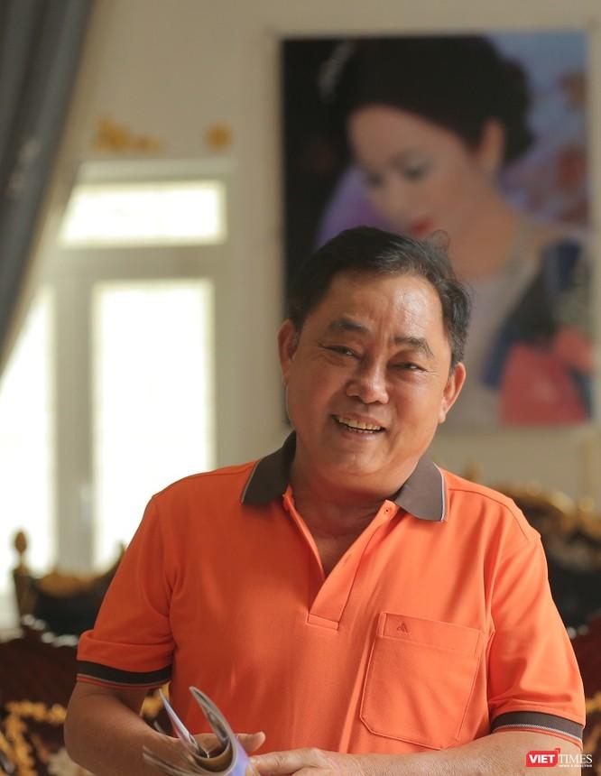 Ông Huỳnh Uy Dũng nét mặt rạng rỡ, phía sau là bức ảnh chân dung vợ treo trang trọng trên tường. Ảnh: An Tâm.