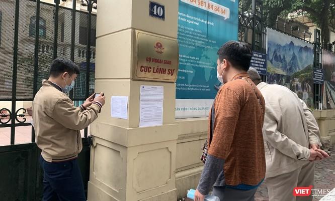Người dân đọc thông báo của Cục Lãnh sự về việc tiếp nhận hồ sơ và trả kết quả qua Bưu điện. Ảnh chụp sáng nay (16/3).
