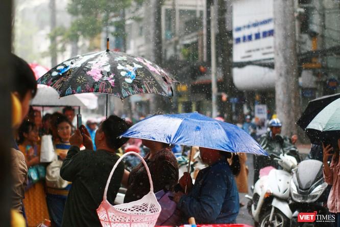 Phía ngoài cổng trường, phụ huynh đội mưa chờ con