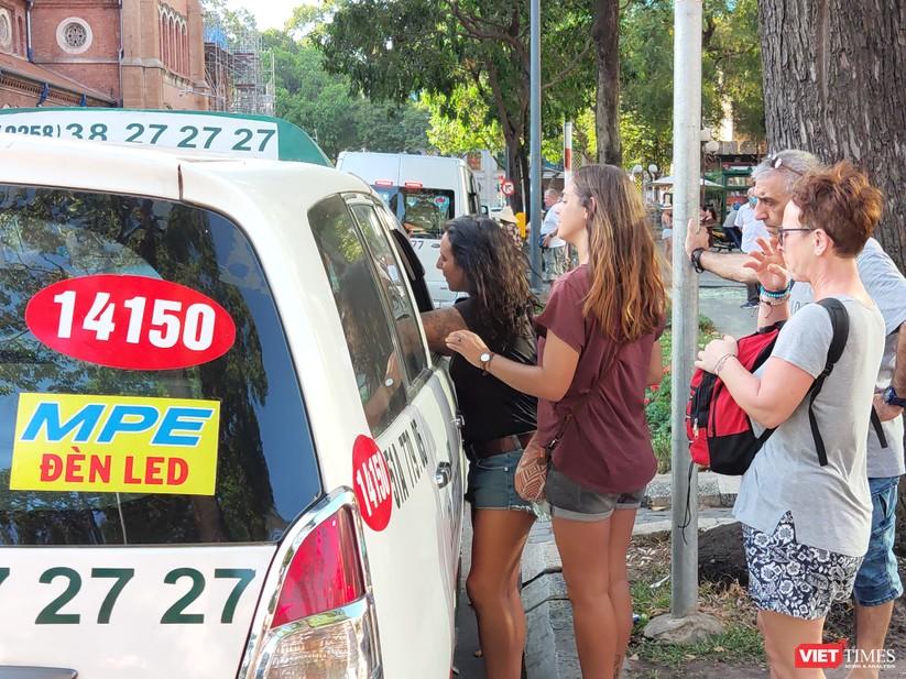 Du khách trò chuyện với lái xe taxi mà không đeo khẩu trang