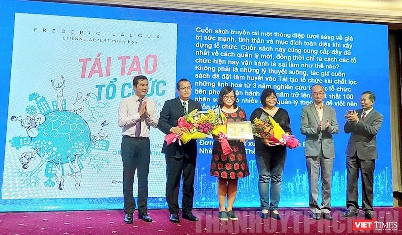 """Giám đốc Sở Công thương TPHCM Bùi Tá Hoàng Vũ (trái) trao chứng nhận sách đáng đọc cho đơn vị xuất bản quyển """"Tái tạo tổ chức"""""""