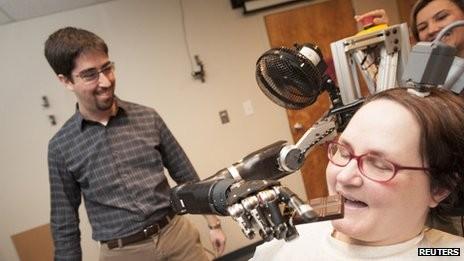 Hình ảnh một phụ nữ bị liệt tứ chi điều khiển một cánh tay robot bằng hệ thống BCI can thiệp. Ảnh: Reuters