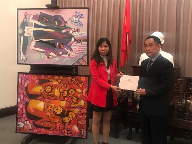 Ông Nguyễn Anh Minh trao giấy chứng nhận tiếp nhận tác phẩm cho đại diện gia đình họa sĩ