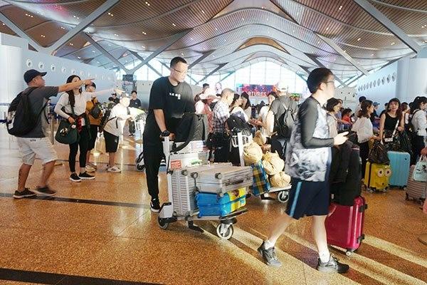 Du khách Trung Quốc làm thủ tục hàng không trước khi về nước tại Sân bay Quốc tế Cam Ranh. Ảnh: Minh Duy