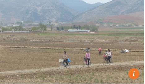 Người dân nông thôn đi xe đạp làm đồng