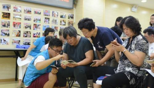 Tình nguyện viên đang dạy một nhóm phụ nữ lớn tuổi các bước để sử dụng điện thoại.