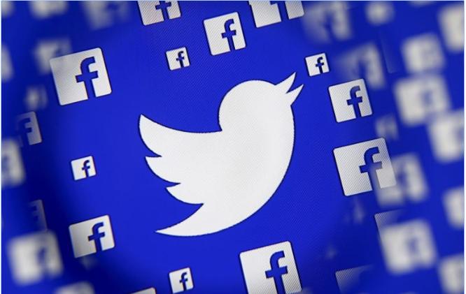 Logo của Facebook và Twitter được phóng đại qua thấu kính trong một minh họa tại Sarajevo, Bosnia and Herzegovina, December 16, 2015. Ảnh REUTERS/Dado Ruvic