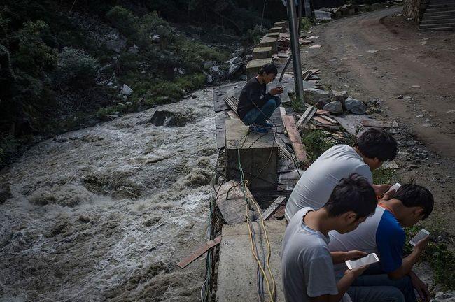"""Hình 13: Thú vui giải trí duy nhất của những """"công nhân"""" ở khu mỏ này chính là sử dụng điện thoại để lên mạng"""