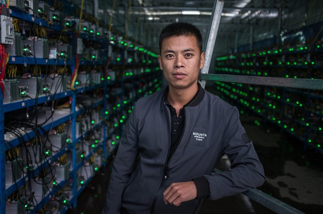 """Hình 3: Kun - chàng trai người Tây Tạng – là chủ nhân của khu mỏ này đang chụp ảnh giữa hai hàng """"trâu cày"""" Bitcoin. Anh cho biết anh được biết về Bitcoin thông qua một người bạn và đã bắt đầu đầu tư vào lĩnh vực này kể từ năm 2015"""