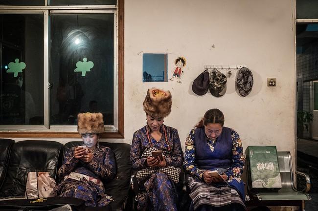 Hình 7: Những người phụ nữ Tây Tạng đang ngồi chờ tham dự một bữa tiệc do Kun tổ chức nhằm ăn mừng việc mở rộng và nâng cấp máy đào Bitcoin.