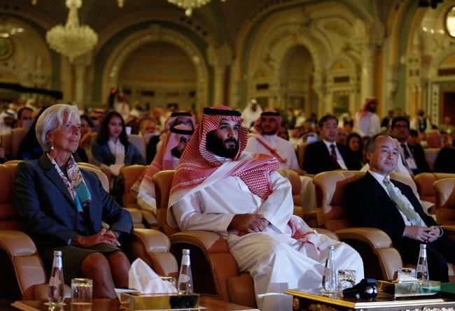Người đàn ông ngồi ở giữa chính là hoàng tử Ả Rập Mohammed bin Salman. Bên phải hoàng tử là ông Masayoshi Son, người đồng sáng lập và điều hành ngân hàng Soft Bank. Bên trái chính là bà Christine Lagarde, giám đốc điều hành Quỹ tiền tệ quốc tế (IMF)