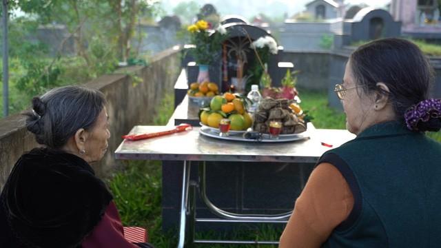 Hai người mẹ ngồi trước mộ con trước giờ khai quật (ảnh: VTV)