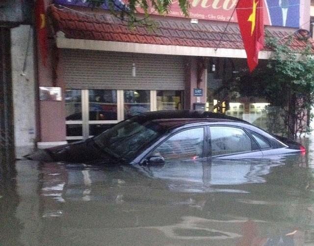 Một chiếc ô tô ngập sâu trong nước trên đường Xuân Thủy - Cầu Giấy
