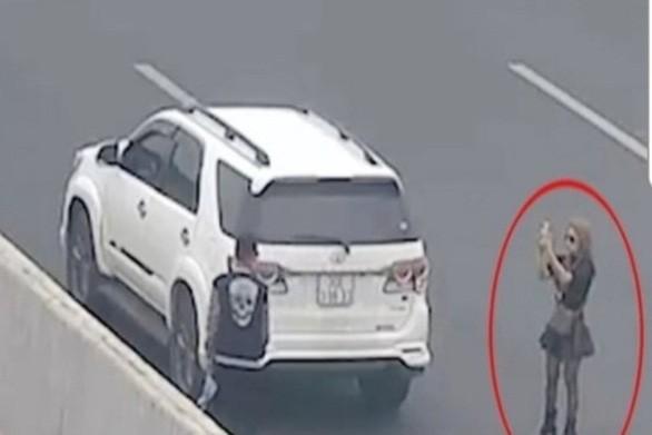 Người phụ nữ chụp ảnh cho bạn ngay trên đường cao tốc, bị camera ghi lại - Ảnh cắt từ camera Cục Cảnh sát giao thông