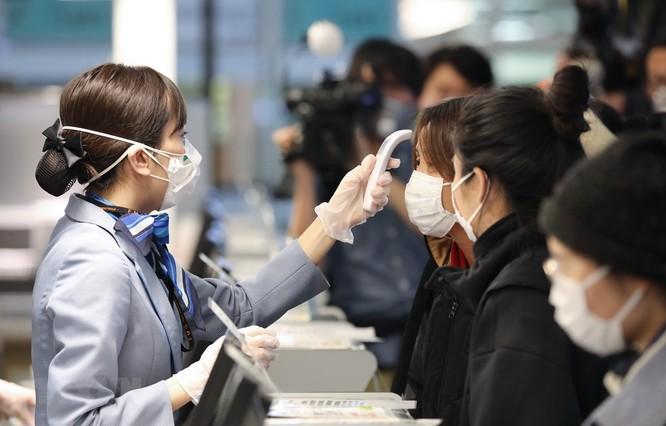 Nhân viên hàng không kiểm tra thân nhiệt các hành khách trước khi họ về Vũ Hán tại sân bay quốc tế Tokyo, Nhật Bản. (Ảnh: THX/TTXVN)