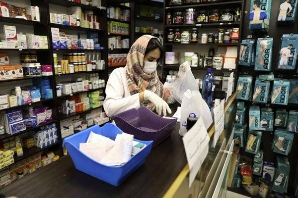 Nhân viên bán thuốc đeo khẩu trang làm việc ở phía tây Tehran. Ảnh: AP.