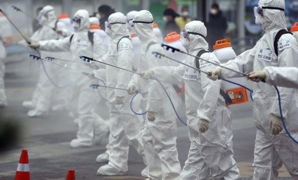 Binh sĩ Hàn Quốc mặc đồ bảo hộ phun thuốc khử trùng ở Daegu. Ảnh: AP.