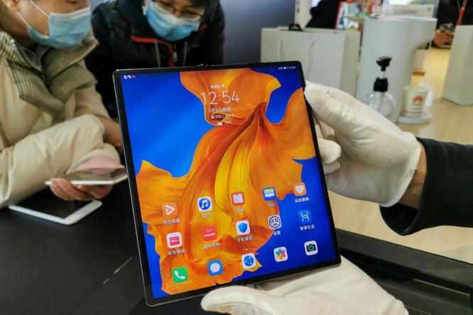 Nhân viên bán hàng đeo găng tay khi giới thiệu smartphone gập Huawei Mate X cho khách hàng hôm 10/3 tại Nam Kinh, Trung Quốc. Ảnh: SIPA Asia