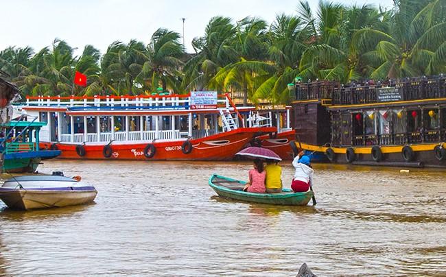 Du khách dong thuyền đi chơi lũ trên sông Hoài