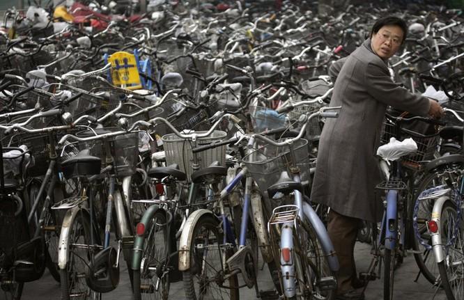 Một phụ nữ lấy xe đạp ở bãi xe ở Bắc Kinh