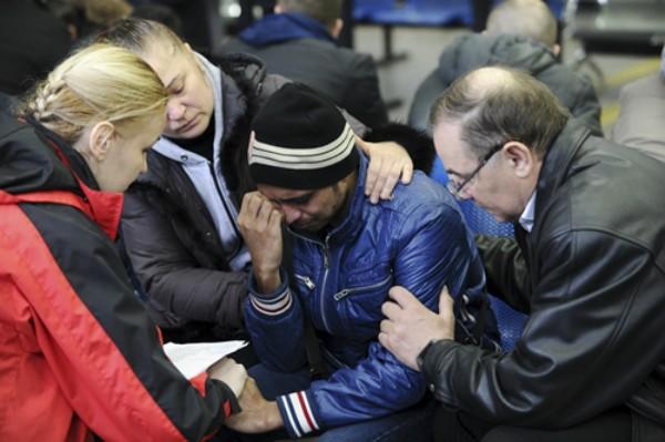 Các bác sĩ tâm lý an ủi người nhà nạn nhân tại sân bay. Ảnh: Reuters