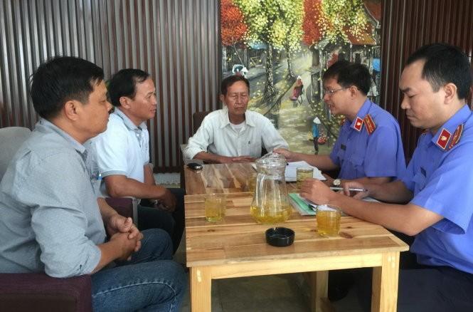 Đại diện VKSND huyện Bình Chánh đang chuẩn bị thủ tục trao quyết định đình chỉ vụ án, đình chỉ bị can với ông Tấn tại quán Xin Chào - Ảnh: Gia Minh