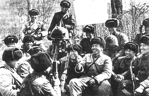 Lính Trung Quốc hả hê trước một chiếc mũ sắt lỗ chỗ vết đạn của biên phòng Liên Xô trong cuộc xung đột biên giới năm 1969