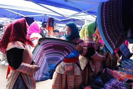 Phụ nữ Mông chọn vải để may trang phục.