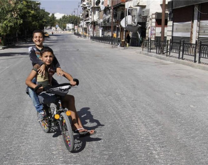 Hai bé trai trên đường phố Aleppo Syria ngày 15/9/2016. Ảnh: Cankao