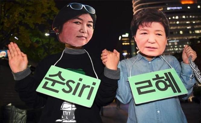 Người biểu tình Hàn Quốc đeo mặt nạ Tổng thống Hàn Quốc Park Geun-hye (phải) và người bạn thân Choi Soon-il trong cuộc biểu tình ngày 27/10/2016. Ảnh: Press TV