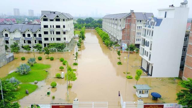 Lối dẫn vào các khu đô thị mênh mông nước. Nhiều người phải bắc ghế để di chuyển qua các đoạn ngập nặng.