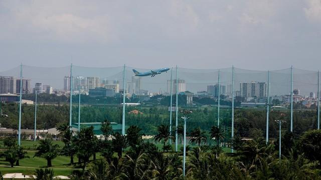 Qua lớp rào lưới chắn bóng, có thể nhìn thấy máy bay đang cất cánh.