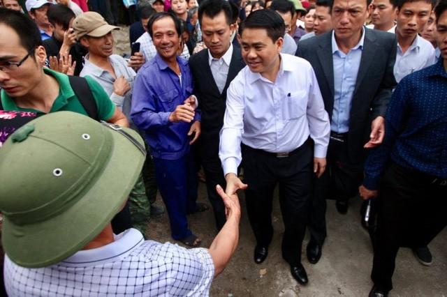 Ông Nguyễn Đức Chung, chủ tịch UBND TP Hà Nội, bắt tay người dân sau khi kết thúc buổi đối thoại với người dân tại thôn Hoành - Ảnh: NGUYỄN KHÁNH
