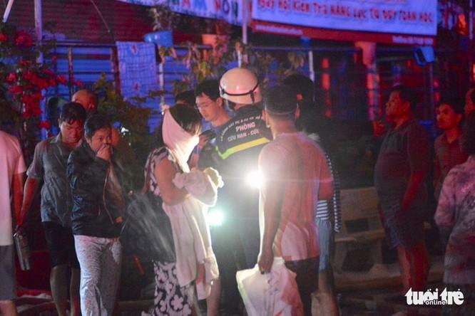 Người dân dùng khăn thấm nước thoát ra khỏi tòa nhà bị cháy lúc rạng sáng 23-3 - Ảnh: LÊ PHAN