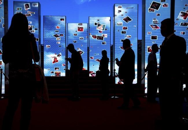 Khách tham quan bước qua các màn hình video tại một triển lãm trưng bày các thành tựu của Trung Quốc đạt được sau 5 năm dưới sự lãnh đạo của chủ tịch Trung Quốc Tập Cận Bình tại Trung tâm Triển lãm Bắc Kinh, Trung Quốc ngày 28.09.2017 (ảnh AP)