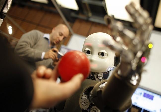 Robot iCub đang cố gắng bắt quả bóng trong sự kiện về ngành công nghiệp robot dịch vụ tại Lyon, Pháp, ngày 15.03.2012 (Ảnh AP)